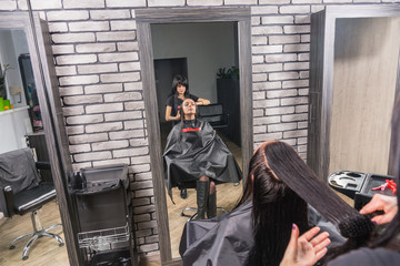 View from above on professional hairdresser combing wet hair of young brunette woman