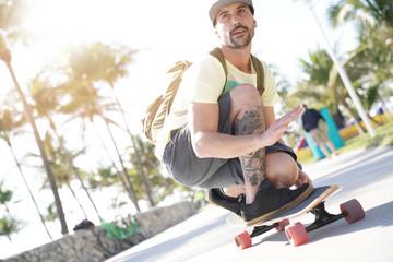 Trendy guy riding skateboard in Miami South Beach promenade