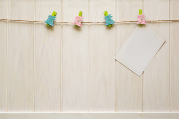Blank cards clipped to clothespins hanging on a wooden background
