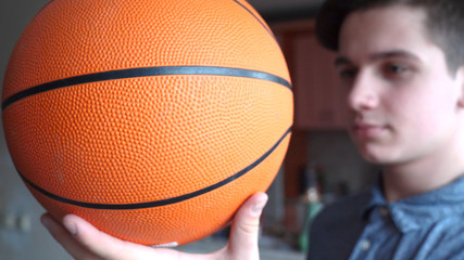 A handsome boy (teenager) is holding a basketball, a brunette with long hair.