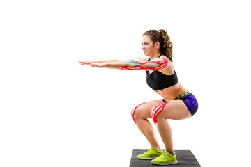 Theme kinesiology tape rehabilitation and health of athletes. Beautiful girl doing a squat exercise on a black rug on a white isolated background. On the arm and knee, a sticky colored ribbon