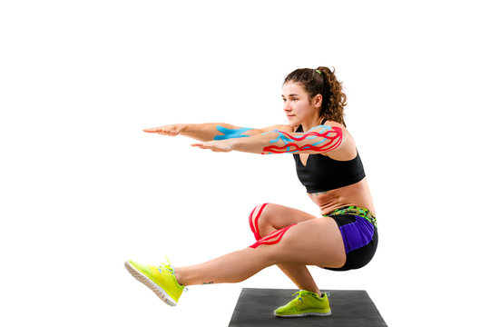 Theme kinesiology tape rehabilitation of athletes. Beautiful girl with beautiful booty doing exercise squatting onblack rug on white background. On arm and knee tape for treatment muscles and tendons