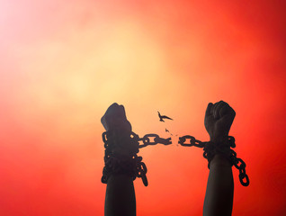 International day for the remembrance of the slave trade and its abolition concept: Silhouette human hands raising and broken chains on blurred red sunset background