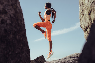 African female athlete jumping and stretching