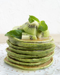 A stack of pancakes with syrup and kiwi.