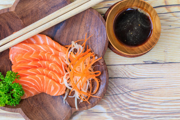 Salmon sashimi in wooden bowl on the table.
