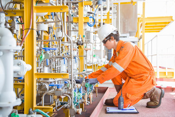 Offshore oil and gas business, production operator logging data and adjusting corrosion inhibitor pump to optimize flow rate for maintain gases and crude oil quality.