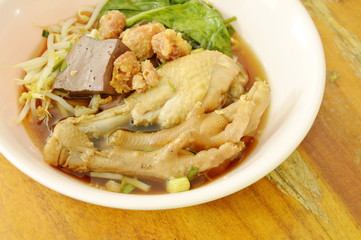 boiled chicken leg and feet with bean sprout in herb brown soup on bowl