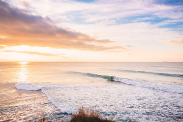 Surfer ride on perfect barrel wave. Landscape with waves and sunrise colors