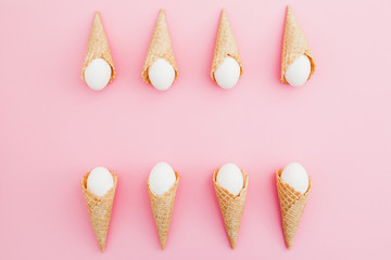 Easter white eggs in waffle cone on pastel pink background. Top view, Flat lay. Easter holiday concept.
