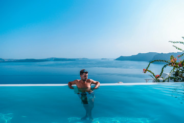 young man at the swimpool during vacation at Santorini Greece