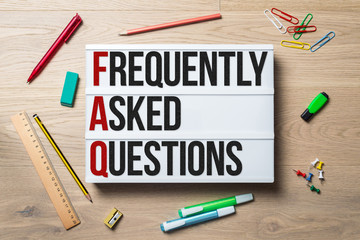 Frequently asked questions written on lightbox lying on desk