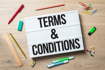 Terms and conditions written on lightbox in office as flatlay