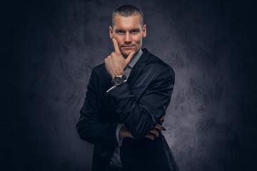Handsome businessman against a dark background.
