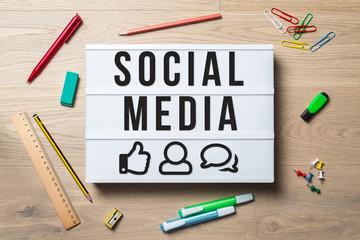 Social media written on lightbox in office as flatlay