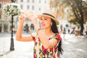 young beautiful girl in summer dress, straw hat. Travels around the European city in the summer. A cheerful, smiling lady talking on a smartphone writes a message photographing the sights. old houses