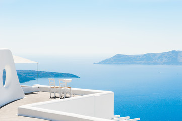 Two chairs on the terrace with sea views. Santorini island, Greece. Travel and vacation background
