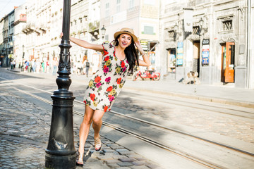 young beautiful girl in summer dress, straw hat. Travels around the European city in the summer. A cheerful, smiling lady