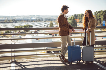 Couple with luggage talking at handrail