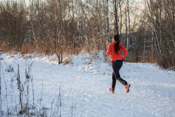 Picture from back of brunette athlete running in winter park