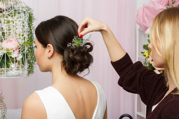 Photo of woman sitting on chair and stylist adjusting hair in pink studio