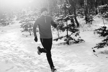 Black and white photo of young athlete running through winter forest