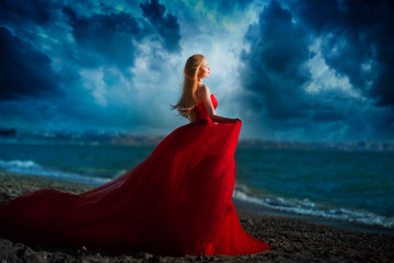 Beautiful girl by the sea. A woman in a red dress on the beach.