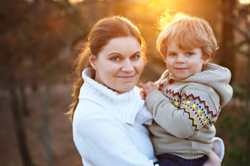Mother and little son in park or forest, outdoors.