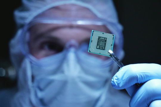 An Ultra Modern Electronic Manufacturing Factory Design Engineer in Sterile Coverall Holds Microchip with symbols in futuristic holography
