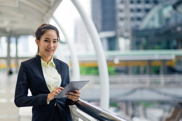 Asian businesswoman with wireless tablet standing outdoors with office building in the background