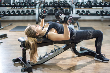 Attractive fitness woman lifting dumbbells while laying on weight bench at gym.