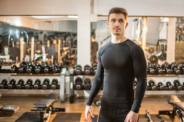 Portrait of young handsome fit man in the gym.