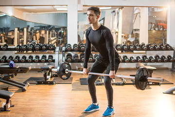 Fit young man lifting barbells in gym.