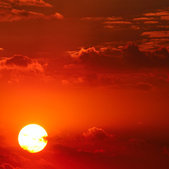 Cloudy sky and bright sun rise over the horizon.