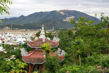 orange roof of the Buddhist pagoda with mountains and city on the background