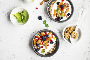 Breakfast, rice porridge or natural yoghurt with assorted berries, fruits and nuts: kiwi, pomegranate, blueberries, almonds, dried apricots in small bowls on a light background. Top view. Copy space.