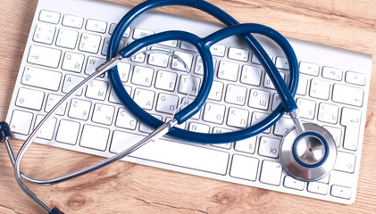 A medical stethoscope near a laptop on a wooden table, on white