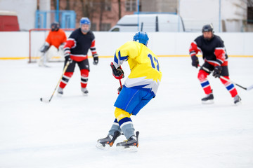 Unrecognizable ice hockey player with stick in attack. Ice hockey game on rink
