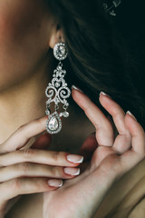 The bride corrects the earring, Beautiful earrings and hands of the bride.