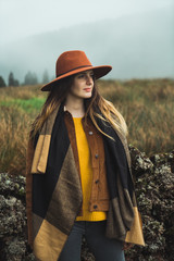 Stylish woman in misty mountains