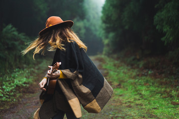 Charming woman with ukulele in nature