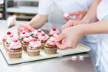 Frauen in Konditorei verzieren Muffins mit Obst