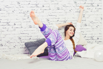 Cheerful young woman in pajamas relaxing at home in bed stretching her arms