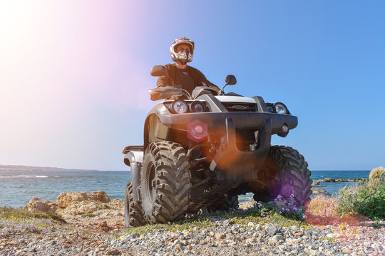 A man is driving ATV on off-road. Sunny.