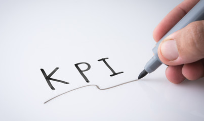 "Hand holding black permanent marker and writing word ""KPI""on white background"