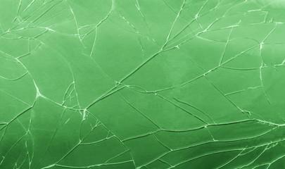 Top view cracked broken green glass texture background.