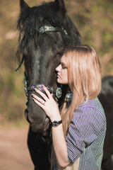young beautiful girl stroking a horse outside
