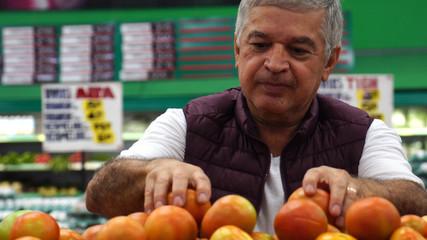 Man Choosing Tomatoes at Supermarket