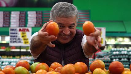 Man Showing Tomatoes at Supermarket