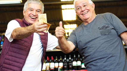 Satisfied Senior Friends Thumbs Up in Supermarket with Brazilian Currency
